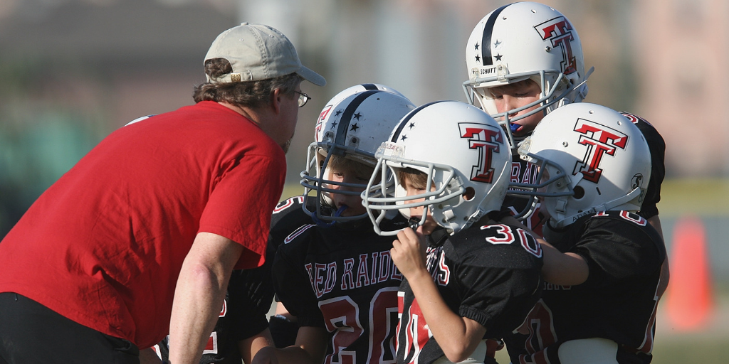 Coach instructing Youth Football team at practice